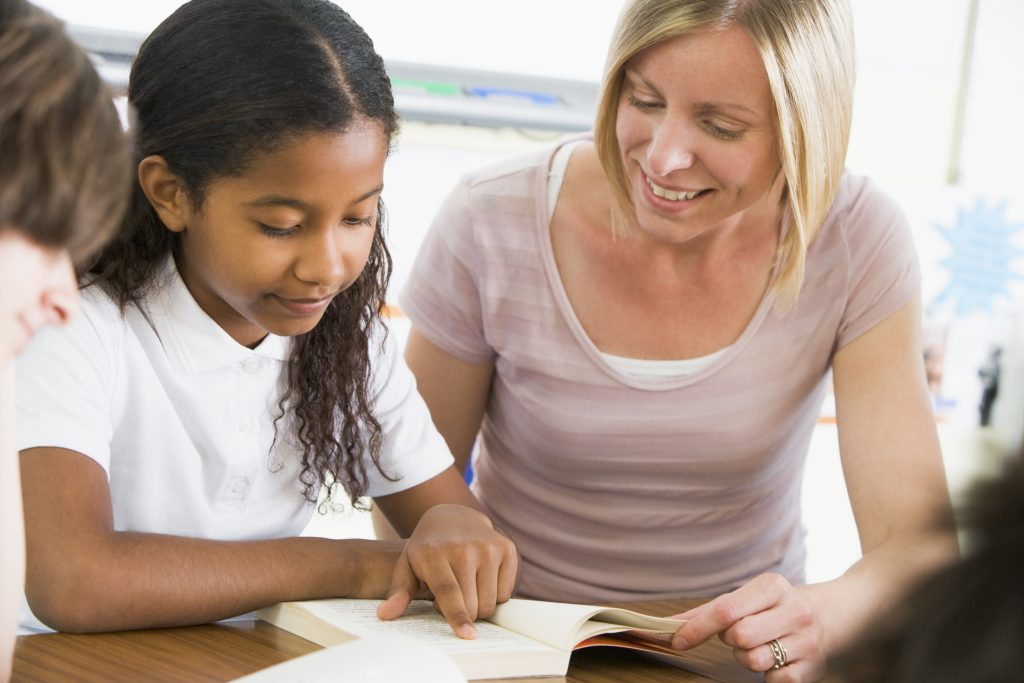 experienced teacher reading with young student