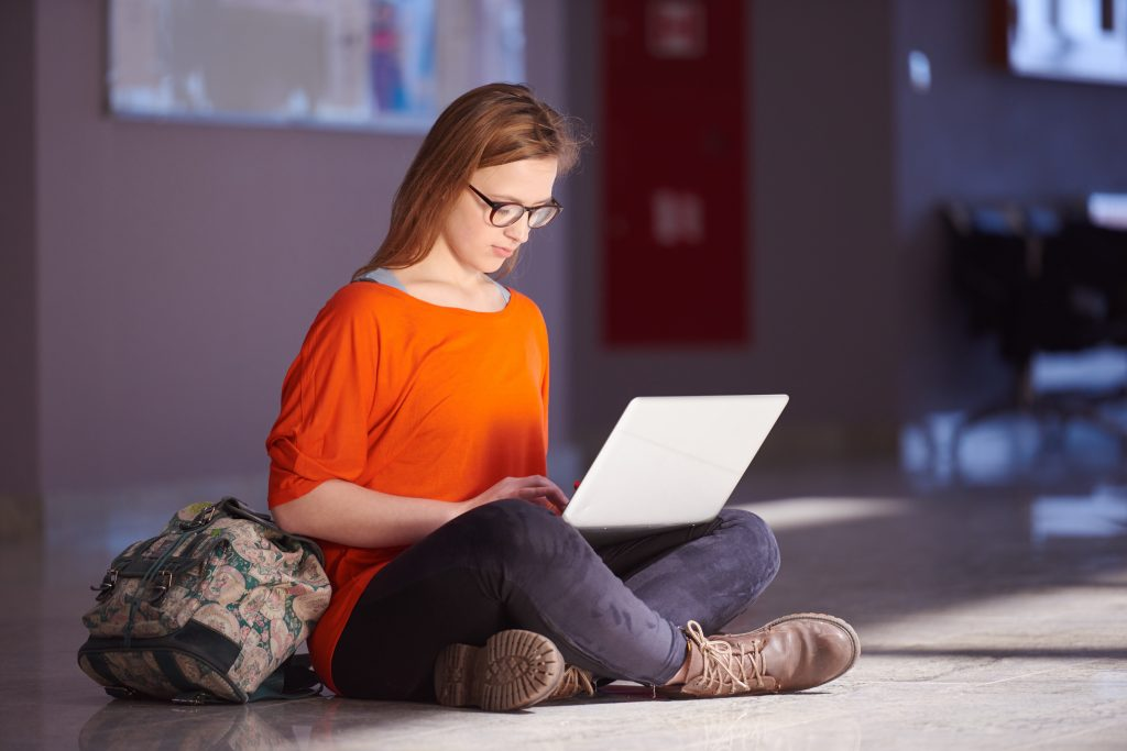 girl sitting on classroom floor using a laptop